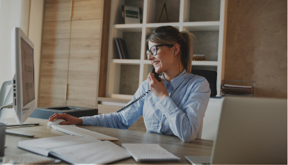 Women with glasses talking on an office phone