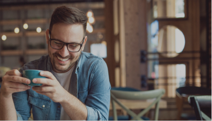 Man in coffee shop laughing about nothing holding a coffee cup